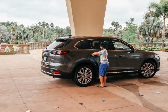 Boy with mouse ears getting into Mazda CX-9
