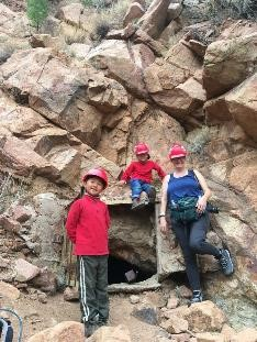 How to plan your family vacation on a budget|Woman with two kids wearing hard hats outside cave