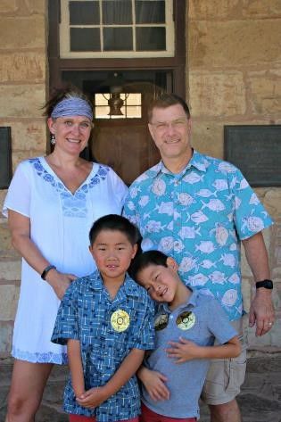 How to plan your family vacation on a budget|Man and woman with two chinese boys all wearing blue