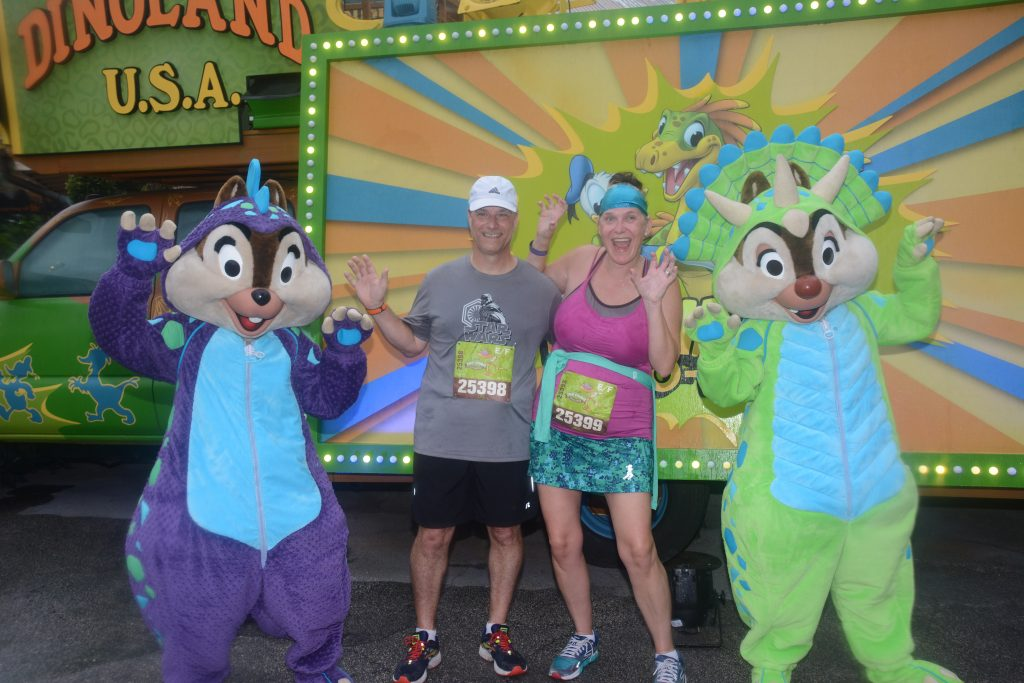 Disney Wine and Dine Half Marathon Weekend - Your Questions Answered|Run Disney Ripped Jeans and Bifocals Man and woman in running clothes with Chip and Dale dressed like dinosaurs