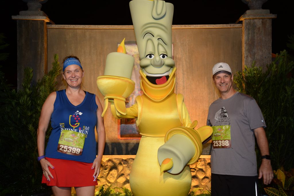 Disney Wine and Dine Half Marathon Weekend - Your Questions Answered|Run Disney Ripped Jeans and Bifocals Man and woman in running clothes with Lumiere from Beauty and the Beast