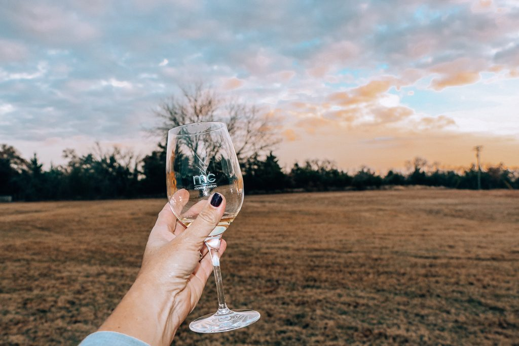 Best places to take Instagram Photos in Decatur Texas|Womans hand with wine glass at sunset at Marker Cellars
