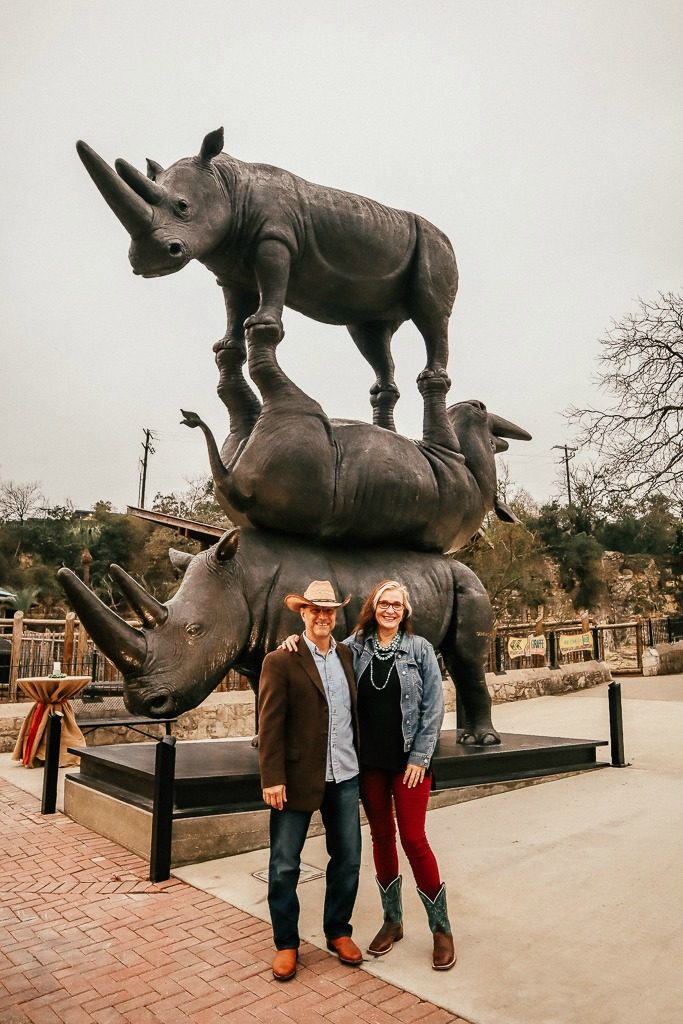 The San Antonio Zoo welcomes two new rhinos|Man and woman in Texas Chic near largest Rhino Sculpture in the World at San Antonio Zoo