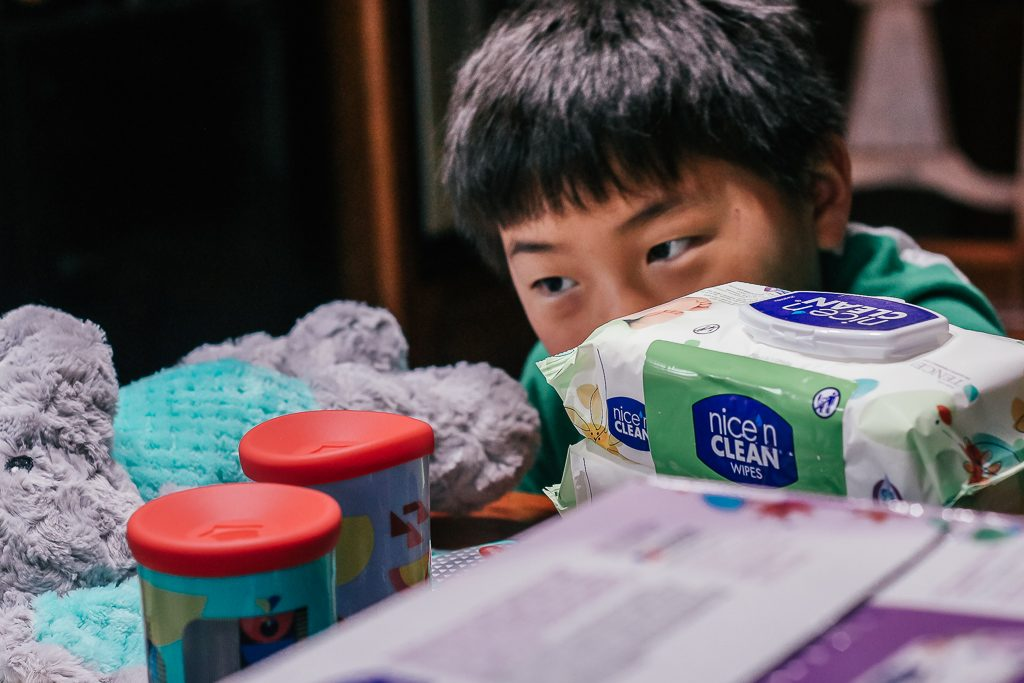 How to get your house ready for a baby...a visiting baby, that is!|Ripped Jeans and Bifocals|Young Asian Boy looking at baby toys on the table with boxes of baby wipes