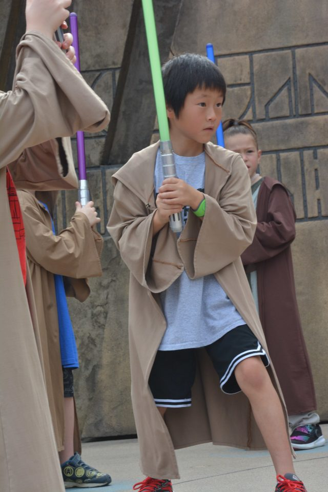 You can sign your kid up for FREE Jedi training? If this isn't a case for Disney World Planning, I don't know what is|Chinese boy with a light sabre