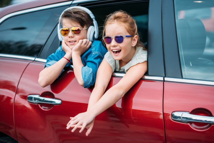 Two kids looking out the window of the car one wearing headphones.