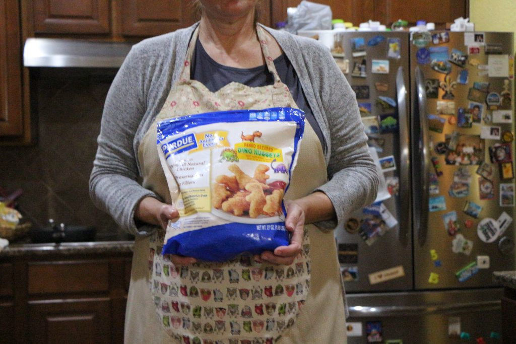 mom in apron holding a bag of Perdue dino nuggets