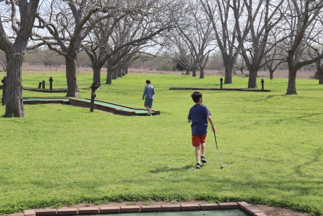 Two boys playing mini golf under the trees
