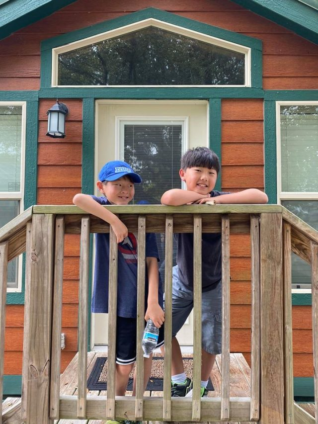 Two boys on the porch of a tiny cabin