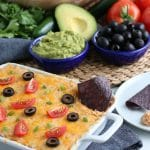 refried bean dip on the table with avocados and olives