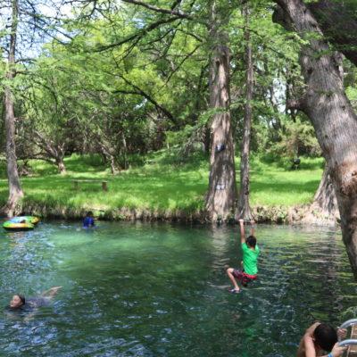 Boy swinging in Blue Hole Texas in Wimberly TX